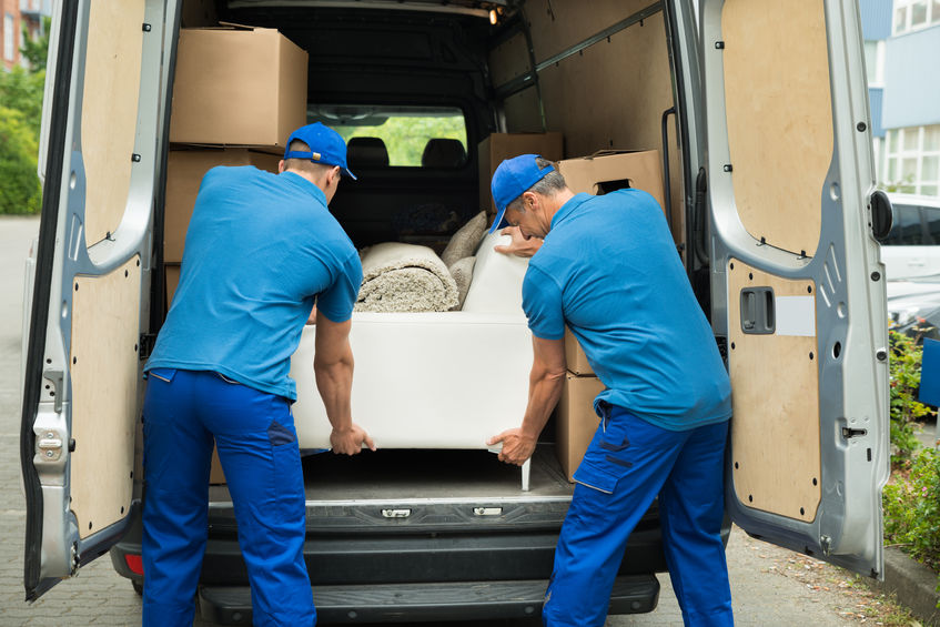 שני סבלים מכניסים ספה למשאית