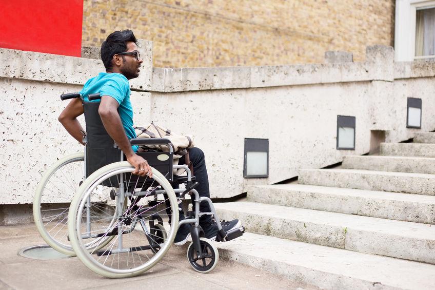 אדם המתנייד עם כסא גלגלים לפני מדרגות